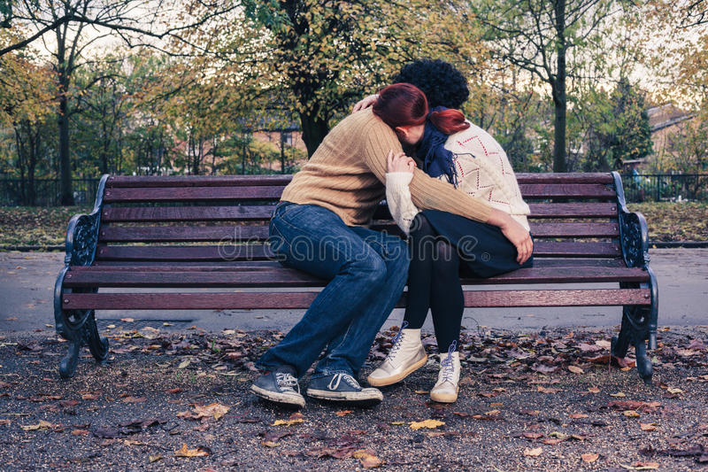Sad young couple on park bench stock image