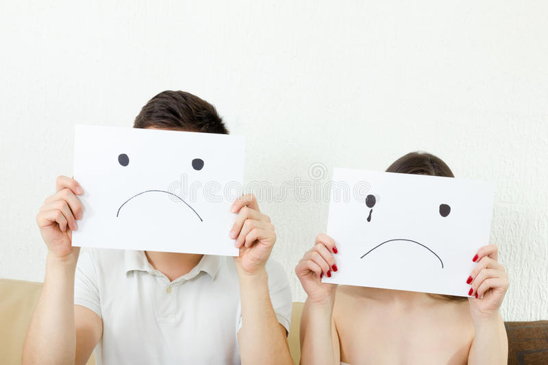 Sad young couple, young couple in despair. Male and female with sad faces. Man and women cover their faces with sad smile drawn on paper with one tear royalty free stock photo
