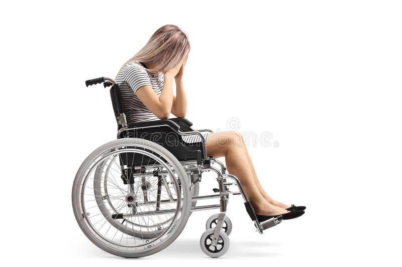 Sad young disabled female in a wheelchair holding her head stock photo