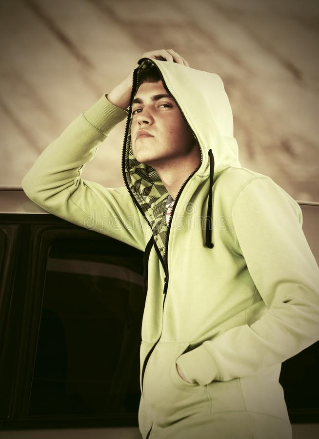 Sad young fashion man standing next to his car. Sad young fashion man in a hoodie standing next to his car stock photography