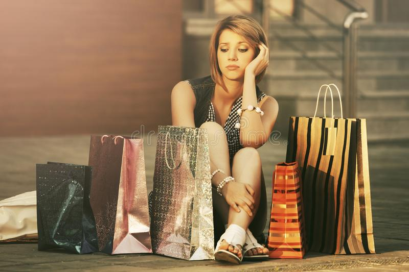 Sad young fashion woman with shopping bags sitting on sidewalk royalty free stock image