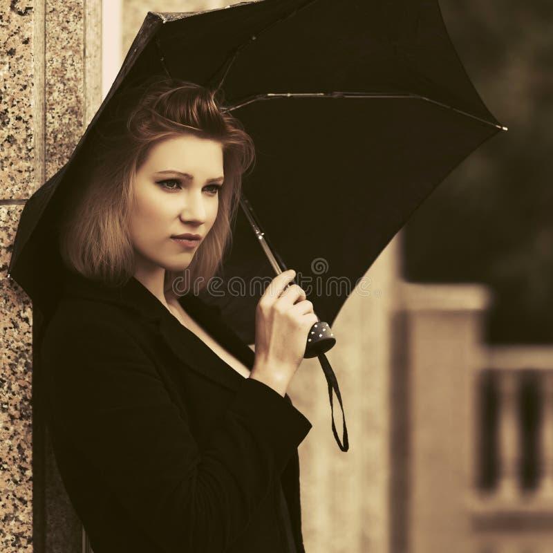 Sad young fashion woman with umbrella on city street. Stylish fashion model wearing classic black coat stock photography