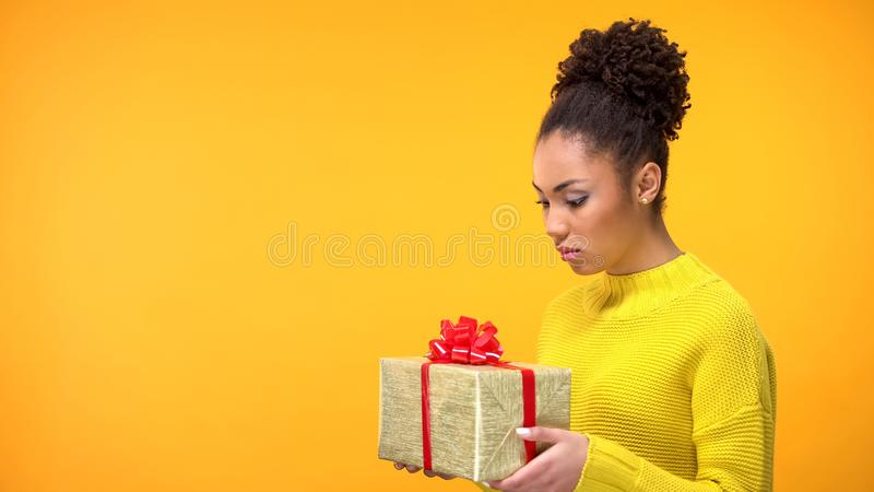 Sad young female looking present in hands, holiday gift disappointment, surprise stock photography