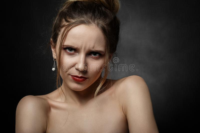 Sad young female. Serious sad young female portrait on black background royalty free stock photography