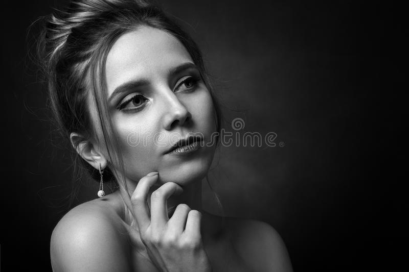 Sad young female. Serious sad young female portrait on black background, monochrome royalty free stock photo