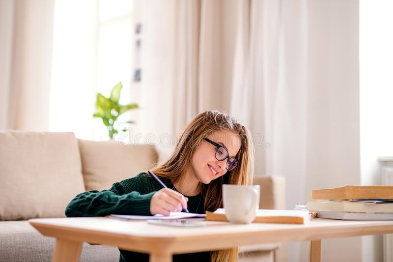 A sad young female student sitting at the table, studying. A young unhappy and sad college female student sitting at the table at home, studying royalty free stock image