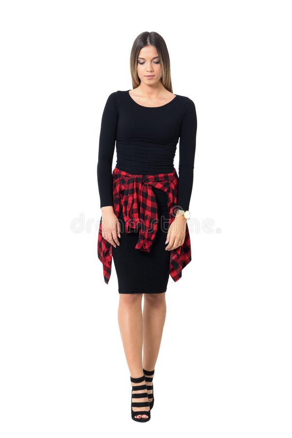Sad young feminine woman in black dress and stiletto walking and looking down. Full body length isolated over white studio background royalty free stock photography
