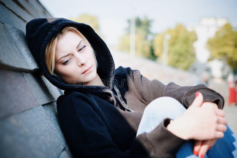 Sad young girl face expression outdoor in urban context stock photos