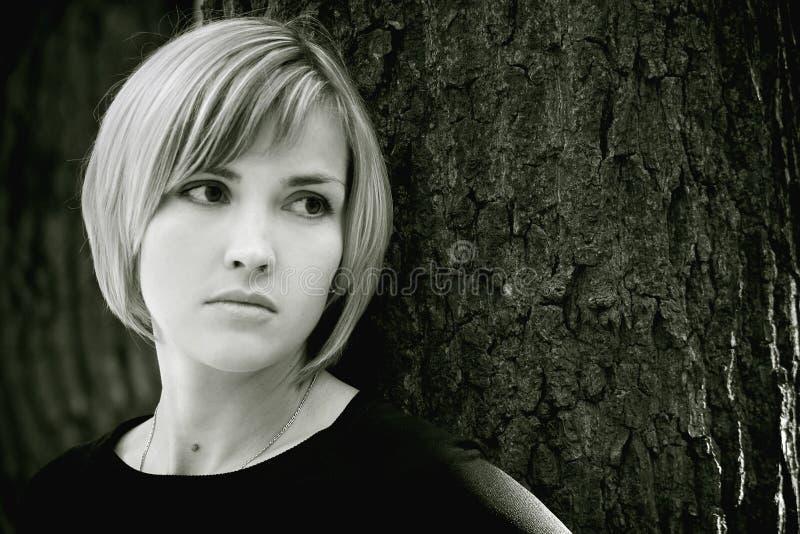 Sad young girl near the tree. Sad young girl with bob haircut near the tree stock image