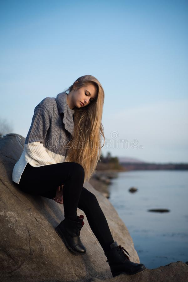 Sad young girl sitting alone on a stone outdoors. Teenage girl thinking thoughtfully. Hope. Sadness. Loneliness stock images
