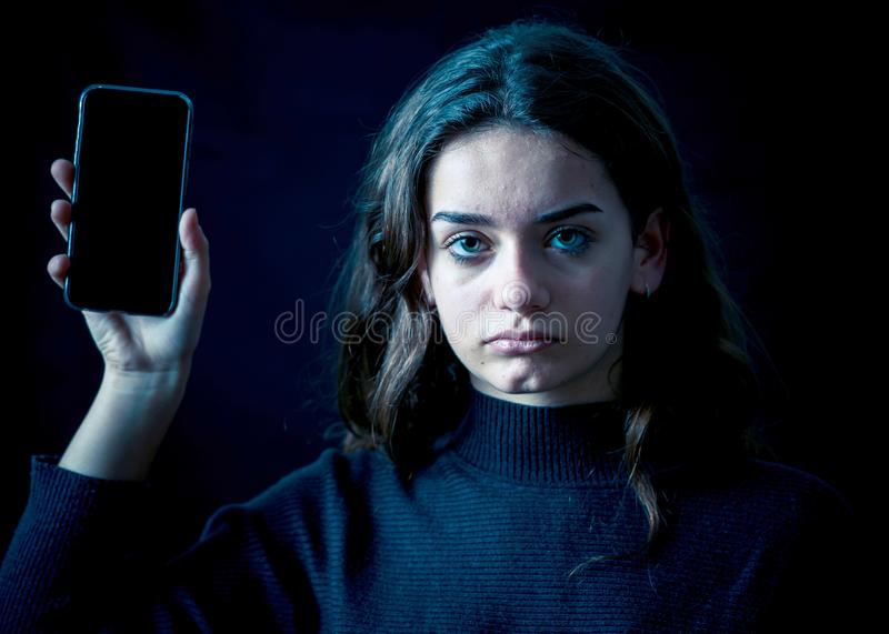 Sad young girl with smartphone suffering harassment online. Onli stock photography