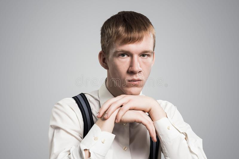 Sad young guy with arms touching his chin royalty free stock images