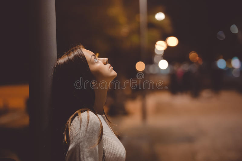 Sad young lady thinking about something leaning royalty free stock photography