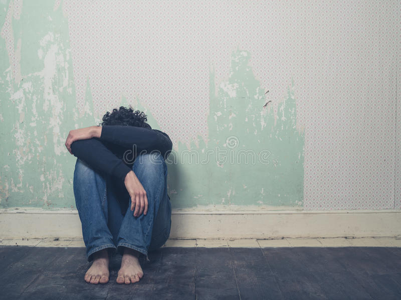 Sad young man in empty room stock image
