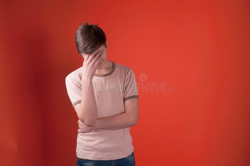 Sad young man feeling headache in beige t shirt standing with hand on forehead. On coral color background with copy space royalty free stock photos
