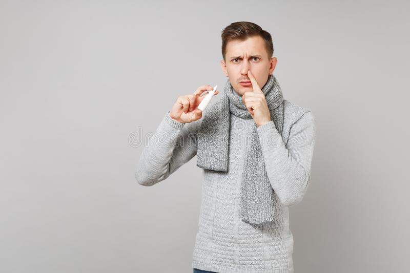Sad young man in gray sweater, scarf holding nasal drops covering nostril with finger on grey background. Healthy lifestyle ill sick disease treatment cold royalty free stock photo