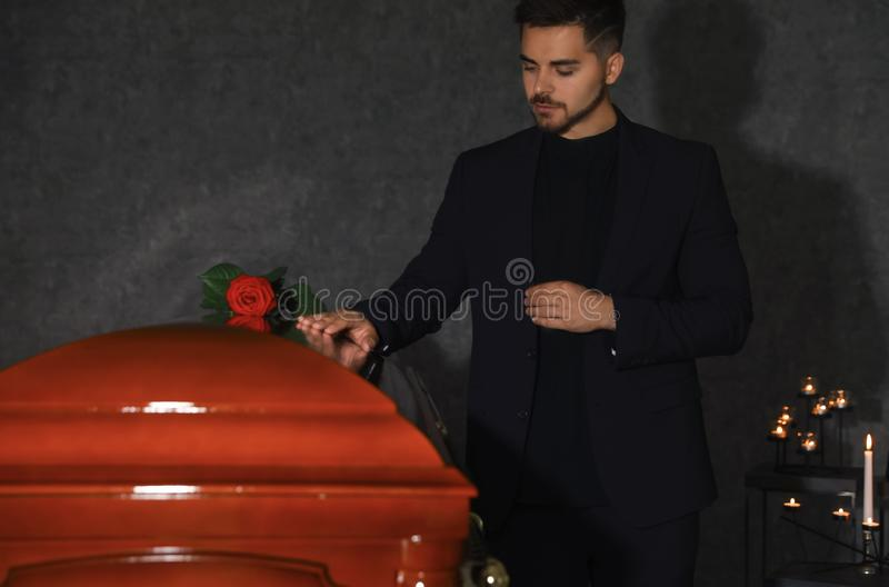 Sad young man near funeral casket with red rose stock photos