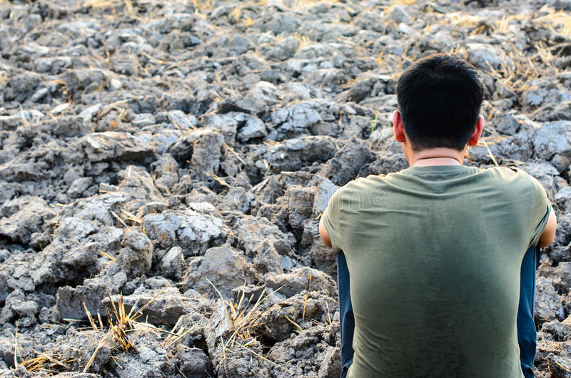 sad young man sitting on barren ground. Look for a dry rice field. royalty free stock image