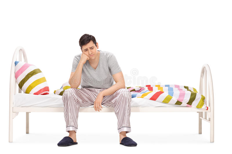 Sad young man sitting on a bed royalty free stock photos