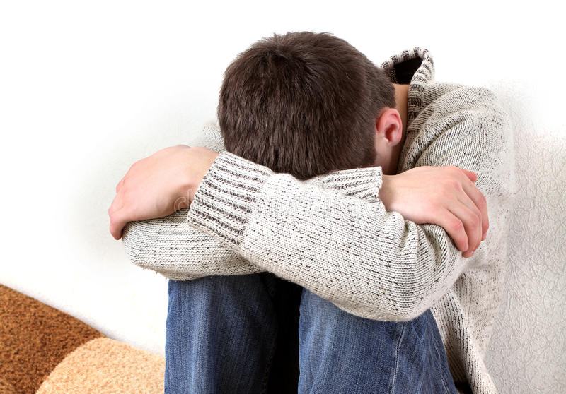 Sad Young Man. Sad Teenager on the Sofa hide the Face and Crying stock photography