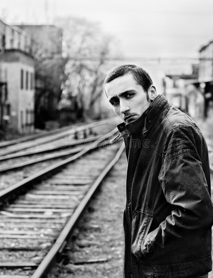 Sad young man waiting for the train among industrial ruins. Black and white royalty free stock image