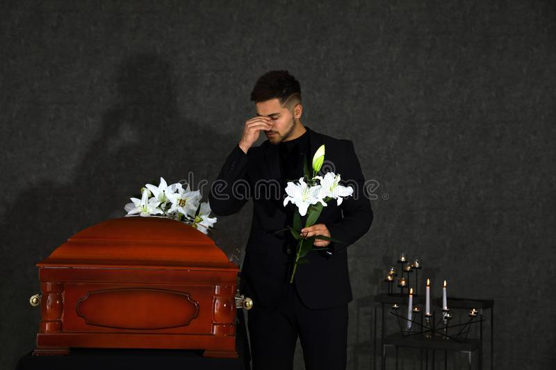 Sad young man with white lilies near casket in funeral stock image