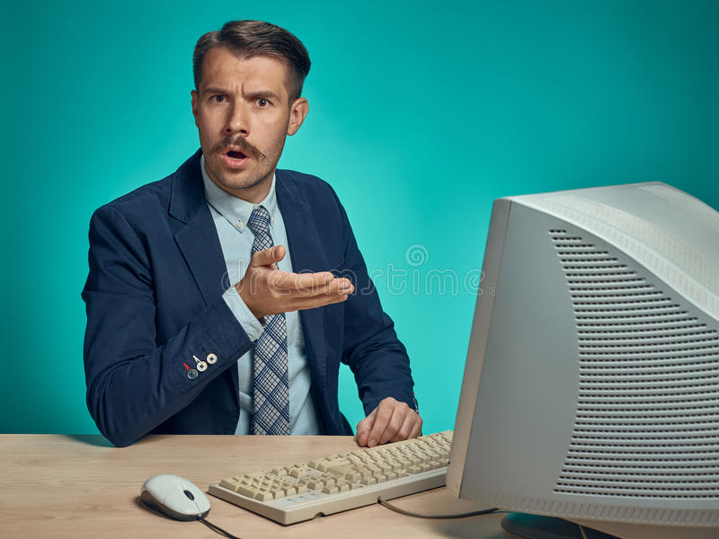 Sad Young Man Working On computer At Desk. The sad young man in a business suit working on computer at desk on blue studio background stock photos