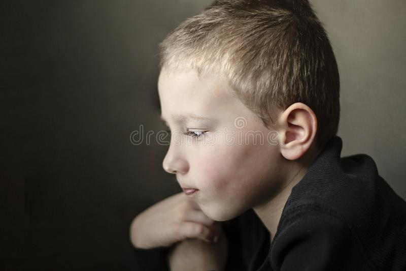 Sad young pre-school boy looking down and thinking. Unhappy child with sad face on dark background. Close-up portrait of depressed young pre-school boy in black stock photos