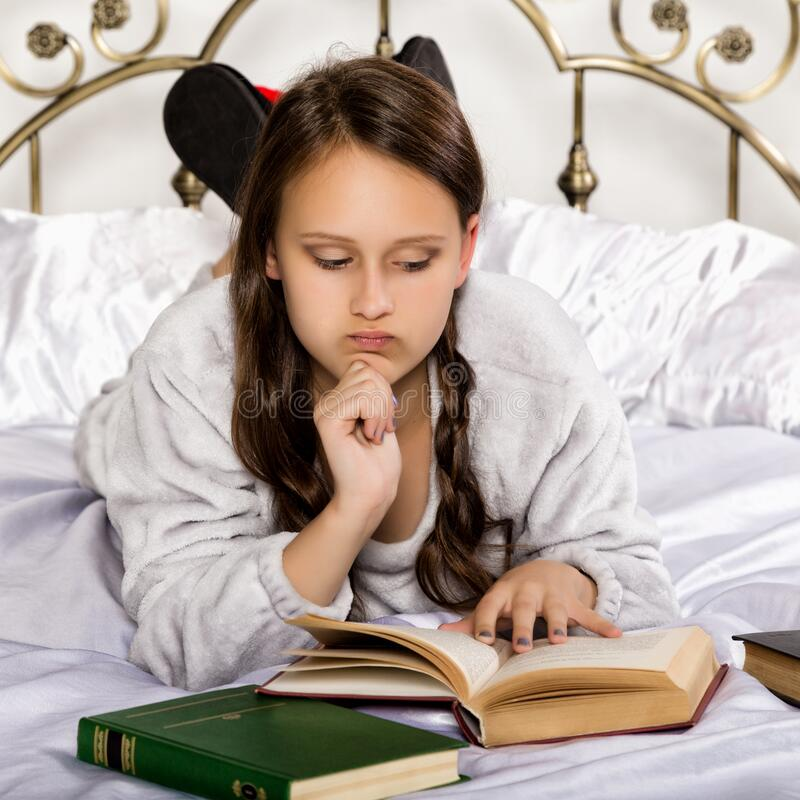 Sad young student girl reads a book while lying on a bed doing homework royalty free stock images