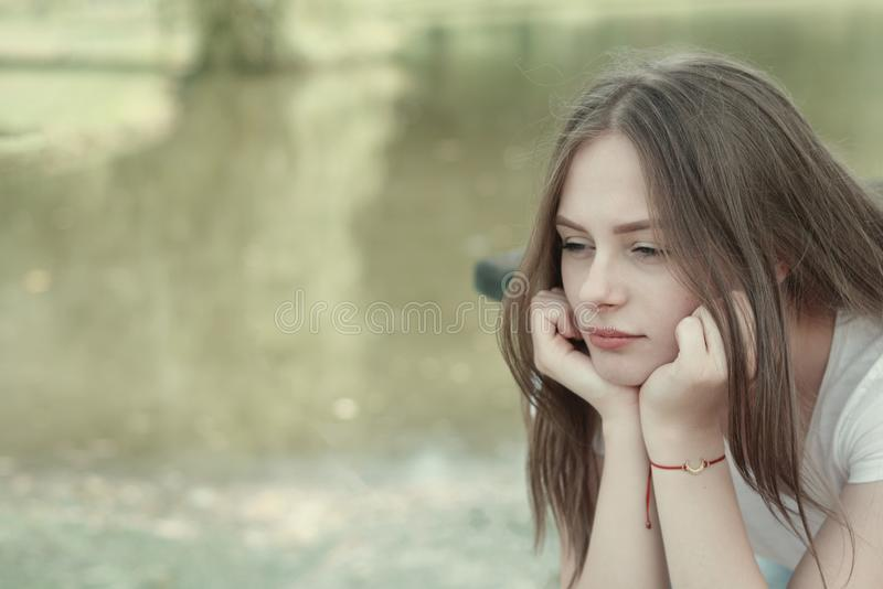 Sad young, teen age girl. Close up portrait of woman meditating. Outdoor scene. Copy space. Sad young, teen age girl. Close up portrait of woman meditating royalty free stock image