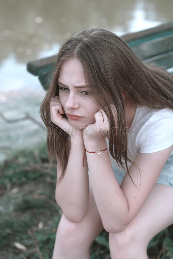 Sad young, teen age girl. Close up portrait of woman meditating. Outdoor scene. Teen age problems, teenage, sadness, beach, park, parenting, education, person royalty free stock photos