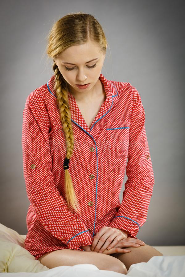 Sad young teenager woman sitting on bed royalty free stock photography