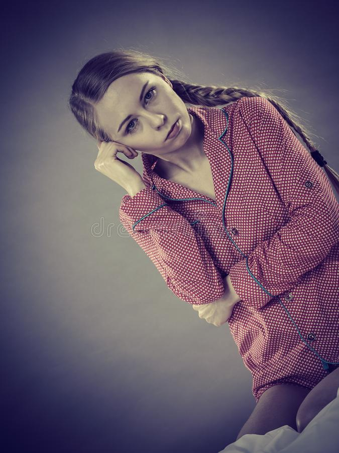 Sad young teenager woman sitting on bed stock photos