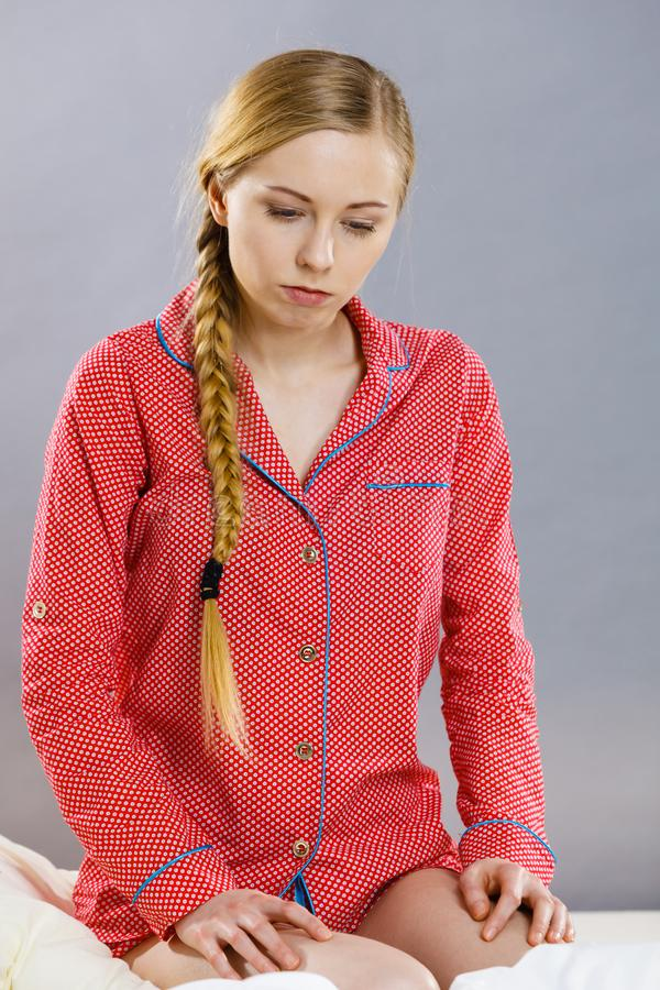 Sad young teenager woman sitting on bed stock photography
