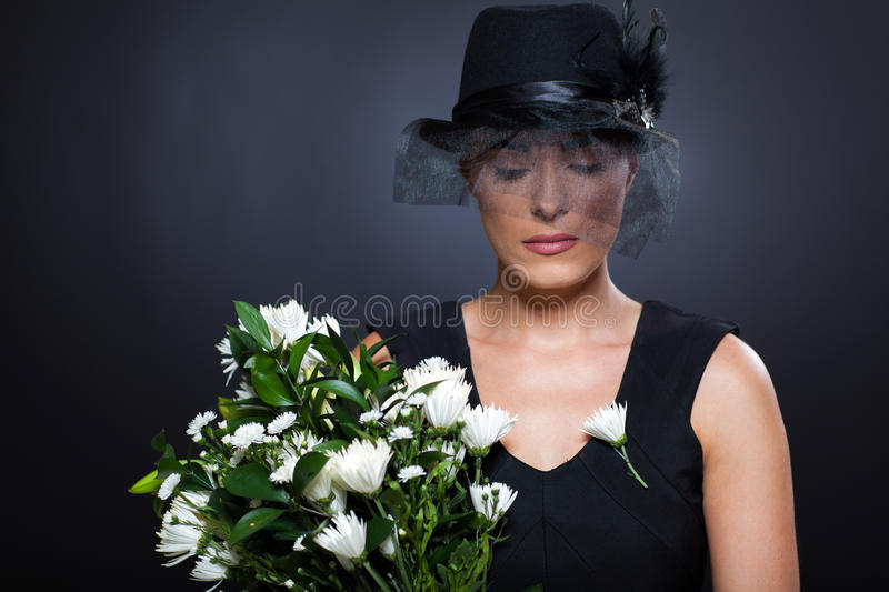 Widow with flowers. Sad young widow with black mourning hat and flowers royalty free stock photos