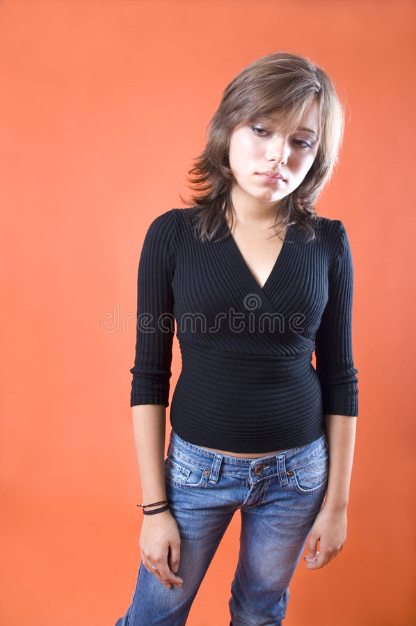 Sad Young Woman. With downcast eyes, averted to her right. Isolated on peach-colored background royalty free stock photos