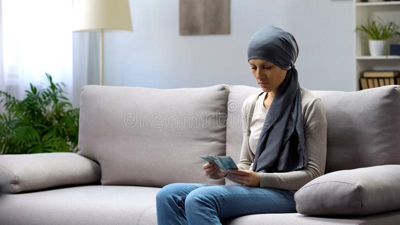 Sad young woman with cancer counting money, insurance, expensive treatment royalty free stock photo