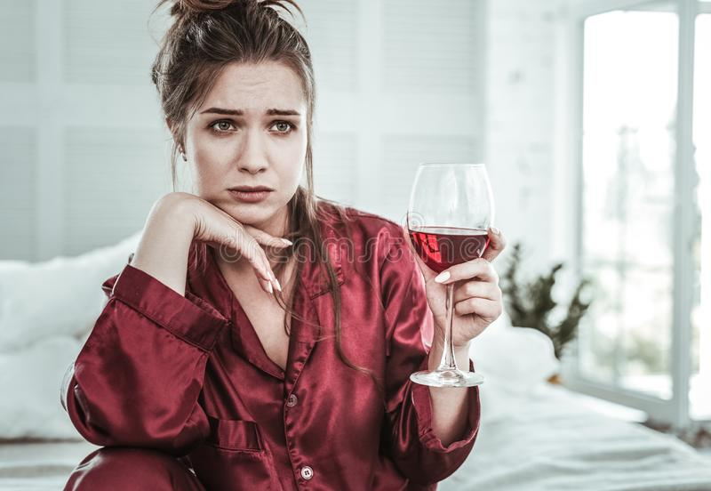 Sad young woman holding a glass of wine royalty free stock images