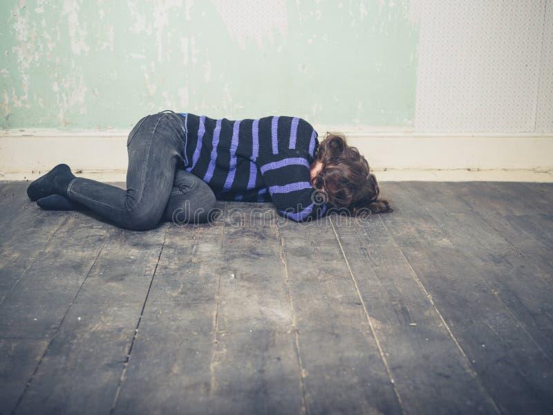 Sad young woman lying on floor stock photography