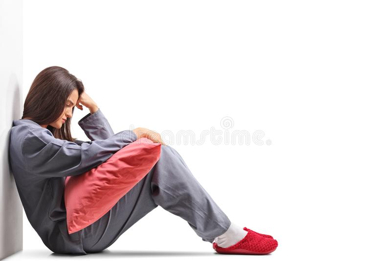 Sad young woman in pajamas sitting on the floor and holding a pi royalty free stock photo