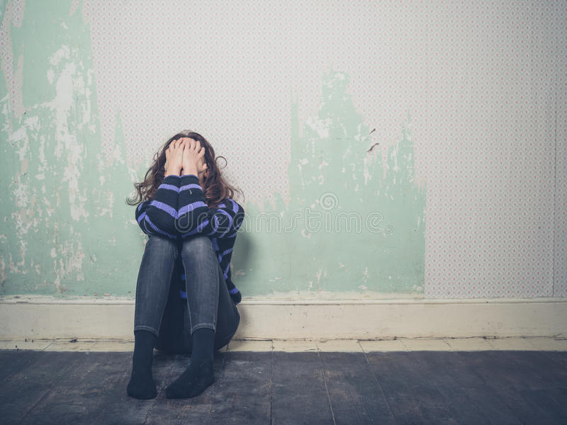 Sad young woman sitting on floor in empty room stock images