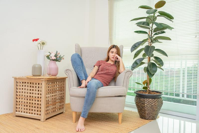 Sad young woman sitting on the sofa near window and flower vase at home, she is depressed and lonely stock image