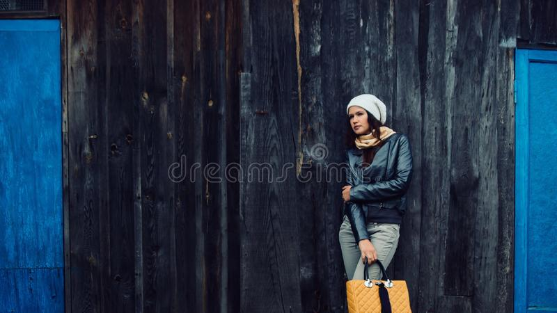Sad young woman standing near an old wooden house royalty free stock photography