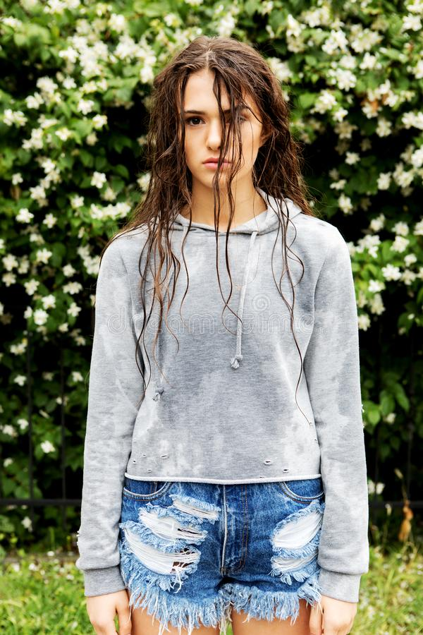 Sad wet woman. Sad young woman standing wet after rain stock photo