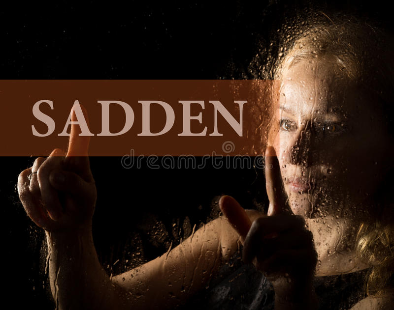 Sadden written on virtual screen. hand of young woman melancholy and sad at the window in the rain. stock photography