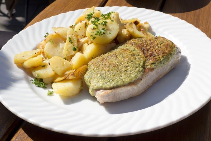 Sadel av grisköttbiff med senap och grillade potatisar arkivfoto