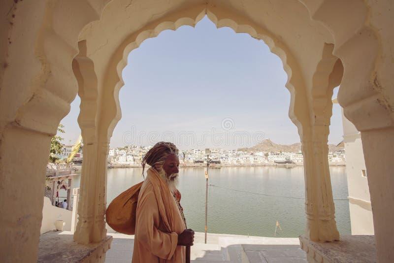 Sadhu Baba com o lago santamente Pushkar foto de stock