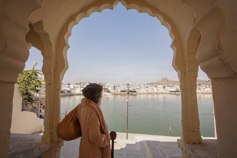 Sadhu Baba com o lago santamente Pushkar fotografia de stock royalty free