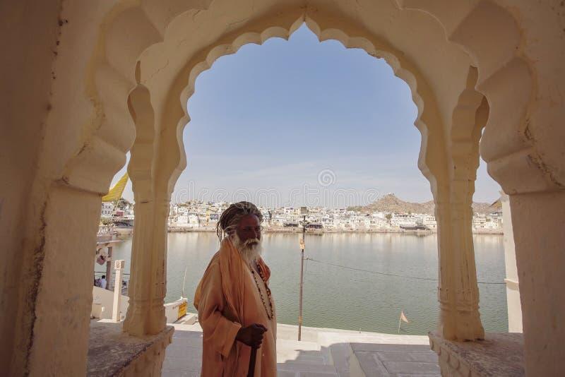 Sadhu Baba com o lago santamente Pushkar fotos de stock royalty free