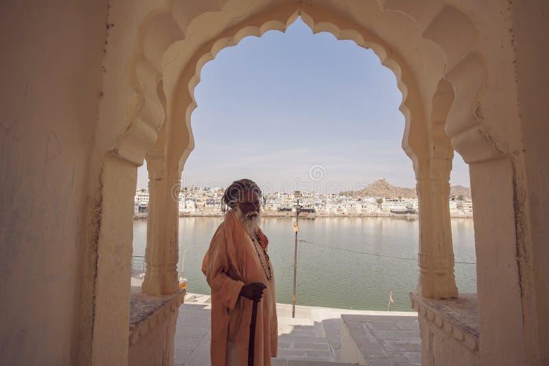 Sadhu Baba com o lago santamente Pushkar imagens de stock